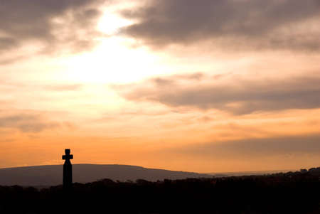 Pink and peach sky over Celtic cross standing in Whitby graveyard, North Yorkshire, England.