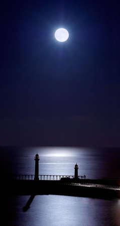 Whitby Piers by moonlight. Stock Photo
