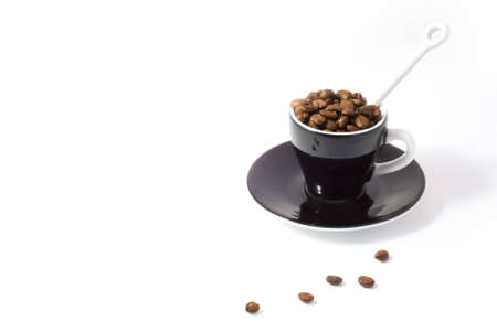 tonne: Espresso cup and saucer containing coffee beans isolated on white background with clipping path