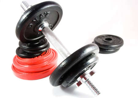 Stack of free weights with dumbbell resting on top. [Isolated on white.]
