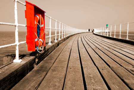 lifebelt: Whitby pier in sepia with red lifebelt Stock Photo