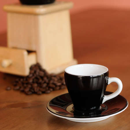 Espresso cup and saucer with coffee grinder with beans in background on wooden kitchen table photo