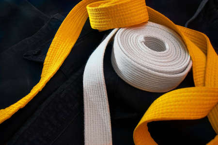 gi: White and yellow karate belts coiled on a folded black gi
