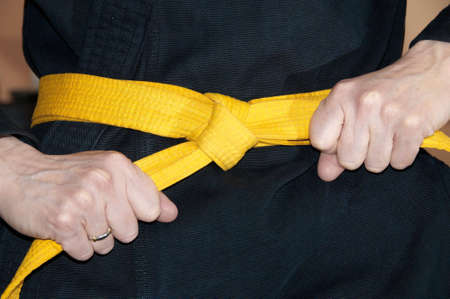black belt: Girl in karate gi tightening yellow belt