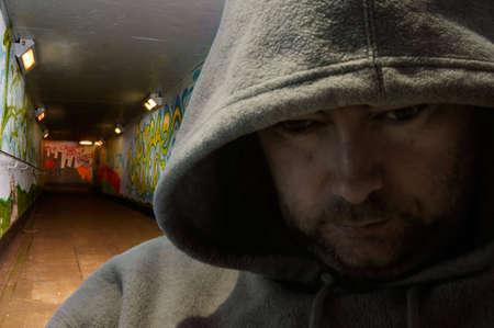 Portrait of man in hoody looking sinister - deliberately dark