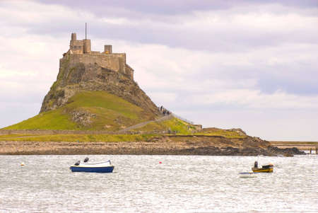 Lindisfarne Castle with boats in Holy Island harbour Stock Photo