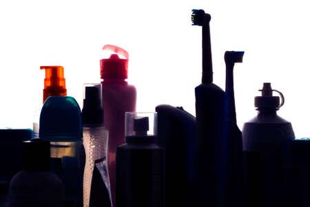 Beauty and hygiene products silouhetted on shelf of bathroom cabinet looking like a city skyline