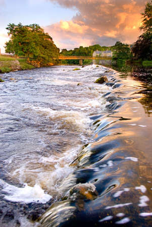 wharfedale: Water running over weir at evening at Grassington, Yorkshire Dales National Park, North Yorkshire, England