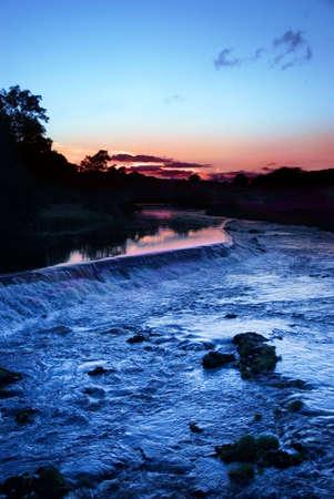 wharfedale: El agua corriendo sobre azud a la puesta del sol en Grassington, Yorkshire Dales National Park, North Yorkshire, Inglaterra