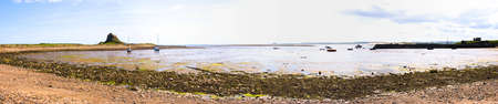 Panorama of Holy Island harbour and Lindisfarne Castle with tide out