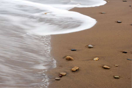 Waves washing over pebbles at Sandsend, Whitby, North Yorkshire, England, UK