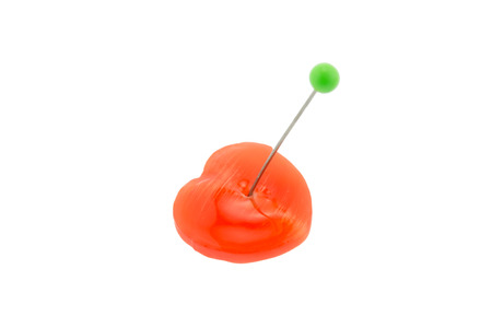 Orange heart candy is stabbed with the green pin on white background  Heart for Valentine and love story Stock Photo - 24946469