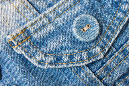 pale color: Smart jeans button in classic and pale color. Blue jeans fabric pocket. Stock Photo
