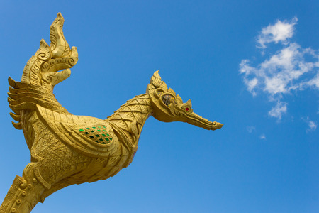 Thai golden swan statue with red eye on blue sky background at corner. Golden swan cement statue in Thai style. photo
