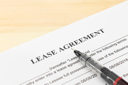 Lease agreement contract sheet and brown pen at bottom right corner on wood table background Banco de Imagens