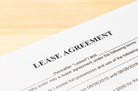 legal document: Lease Agreement Contract Document on Wood Table. Legal document for business event
