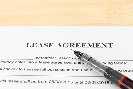 legal document: Lease Agreement Contract Document and Pen Horizontal View on Wood Table. Legal document for business event