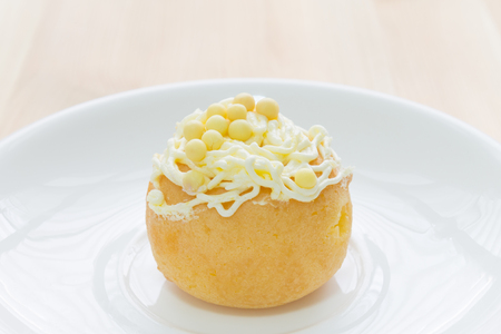profiterole: Yellow choux pastry or cream puff or profiterole that have whipped cream on the head. Eclair dessert on wood table. Stock Photo
