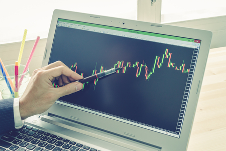 technical analysis: Businessman is pointing stock graph or forex graph . Technical analysis forex or stock by professional trader with pen on Blue Vintage Style