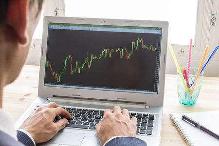 technical analysis: Businessman is analyzing stock graph or forex graph with laptop in old office. Technical analysis by professional Stock Photo