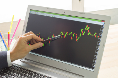 technical analysis: Businessman is pointing stock graph or forex graph . Technical analysis forex or stock by professional trader with pen Stock Photo