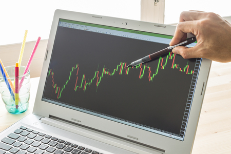 technical analysis: Businessman is pointing stock graph or forex graph . Technical analysis forex or stock by professional trader with pen in right hand Stock Photo