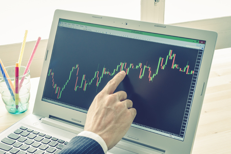 technical analysis: Businessman is pointing stock graph or forex graph . Technical analysis forex or stock by professional trader on Blue Vintage Style
