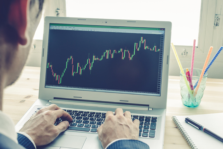 technical analysis: Businessman is analyzing stock graph or forex graph with laptop in old office. Technical analysis by professional on Blue Vintage Style