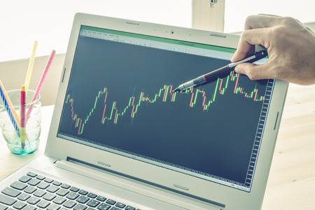 technical analysis: Businessman is pointing stock graph or forex graph . Technical analysis forex or stock by professional trader with pen in right hand on Blue Vintage Style