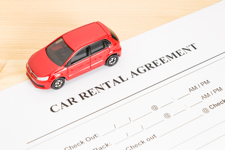 legal document: Car rental agreement with red car on left view. Auto rental agreement or legal document Foto de archivo
