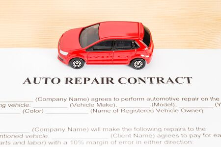 pact: Auto repair contract with red car on center. Car repair agreement or legal document