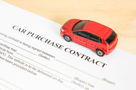 pacto: Car purchase contract with red car on right view. Auto purchase agreement or legal document