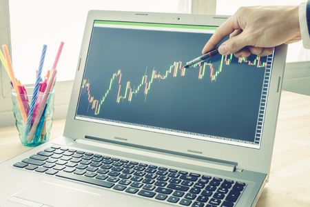 technical analysis: Businessman is pointing stock graph or forex graph . Technical analysis forex or stock by professional trader with pen in right hand in vintage style