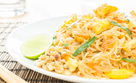 placemats: Pad Thai or Thai fried noodles on white dish and bamboo placemats. Chopsticks and glass and egg dry shrimps onions sprouts lemon peanut Stock Photo