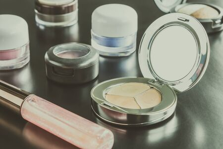 face powder: Woman cosmetics include lip gloss and eyeshadow and foundation or face powder on black floor classic style Stock Photo