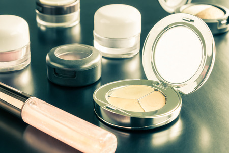 face powder: Woman cosmetics include lip gloss and eyeshadow and foundation or face powder on black floor vintage style Stock Photo
