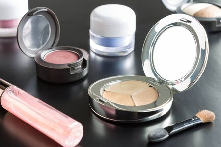face powder: Woman cosmetics include lip gloss and eyeshadow and foundation or face powder and brush on black floor