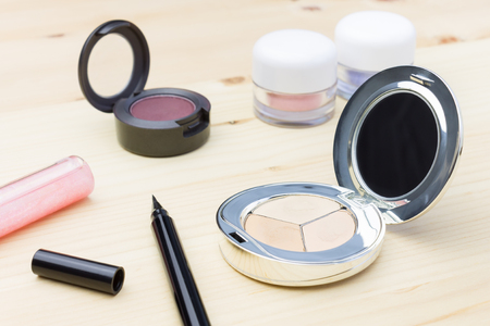 face powder: Woman cosmetics include eyes liner and lip gloss, and eyeshadow and foundation or face powder on wood table Stock Photo