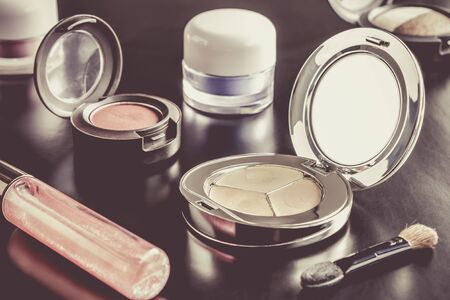 face powder: Woman cosmetics include lip gloss and eyeshadow and foundation or face powder and brush on black floor sweet style