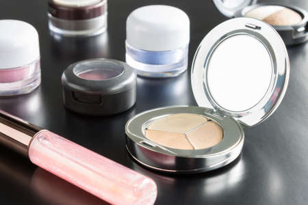 face powder: Woman cosmetics include lip gloss and eyeshadow and foundation or face powder on black Floor
