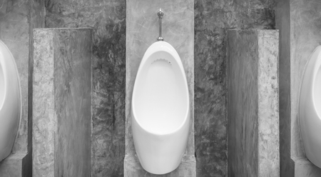 White urinal men with concrete wall loft style for interior design or exterior design. White urinal men in public toilet. Chamber pot or urinal   men classic and retro style in black and white center