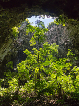 Sun light hole in Phraya Nakhon Cave with green tree and blue sky and cloud at Prachuap Khiri Khan Thailand. Natural cave in unseen Thailand