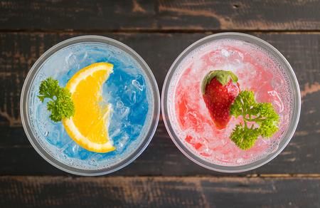 Blue Red Italian Soda Cold Beverage and Lemon Strawberry Fruit and Parsley. Blue Red Italian Soda Cold Beverage on wood table for food and drink category Banco de Imagens - 121633169