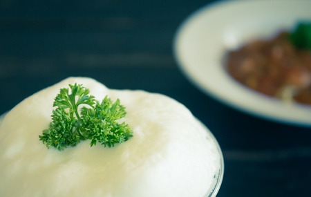 Milk froth and Parsley on Black Wood Table. Milk froth in plastic glass. Milk froth for food and drink category