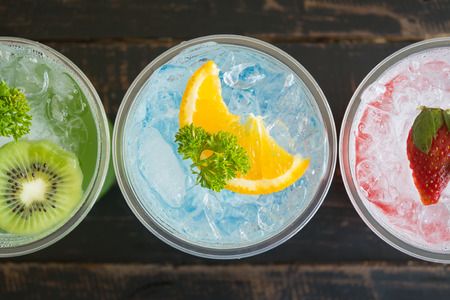 Green Blue Red Italian Soda Cold Beverage and Kiwi Lemon Strawberry Fruit and Parsley. Green Blue Red Italian Soda Cold Beverage on wood table for food and drink category Banco de Imagens - 121633174