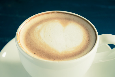 Vintage Heart Shape Froth Milk Latte Art in White Coffee Cup Zoom on Black Wood Table. Heart shape froth milk Latte art hot beverage for coffee lover