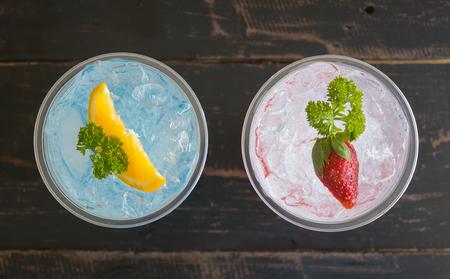Blue Red Italian Soda Cold Beverage and Lemon Strawberry Fruit and Parsley. Blue Red Italian Soda Cold Beverage on wood table for food and drink category Banco de Imagens - 121634587