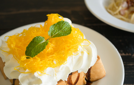 Golden Egg Yolk Threads or Foi Thong Toast and Whipped Cream and Chocolate. Thai dessert golden egg yolk threads or foi thong with peppermint on whipped cream on bread with chocolate sauce for food and drink category