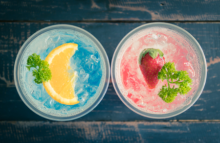Blue Red Italian Soda Cold Beverage and Lemon Strawberry Fruit and Parsley. Blue Red Italian Soda Cold Beverage on wood table for food and drink category Banco de Imagens - 121639718
