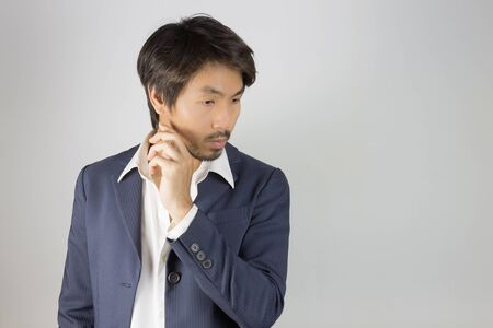 Portrait Man in Navy Blue Suit Looking Below and Touch Chin Pose. Portrait man in navy blue suit and white shirt on left frame of grey background in smart style